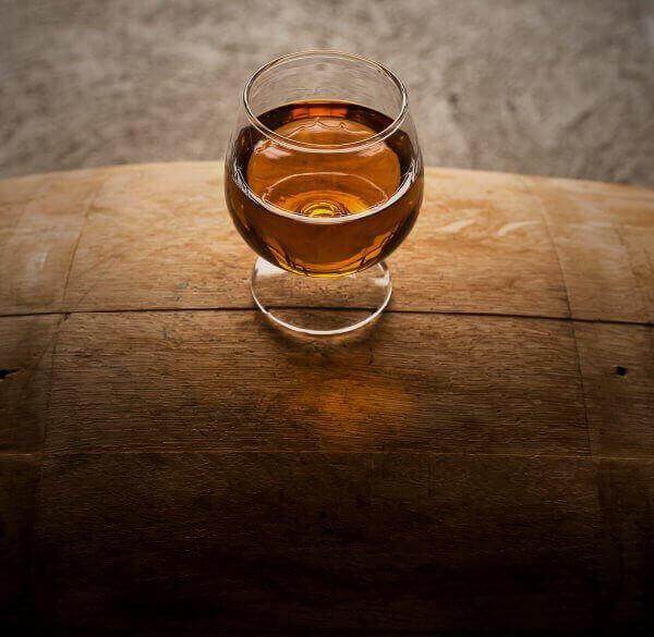 closeup of bourbon snifter with Wilderness Trail Distillery bourbon on top of a bourbon barrel